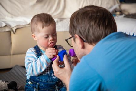 Foto de Cute baby boy with Down syndrome playing with dad - Imagen libre de derechos