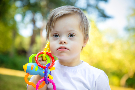 Foto de Portrait of Cute small boy with Down syndrome playing in summer day on nature with toys - Imagen libre de derechos