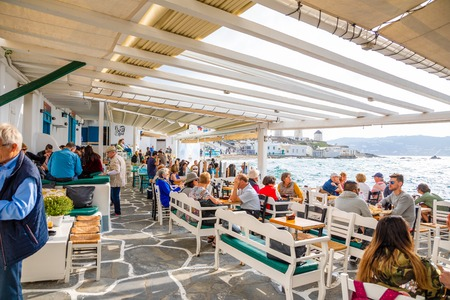 Photo for Mykonos, Greece - 17.10.2018: People in cafe in Famous Mykonos town colorfull little venice, Mykonos island, Cyclades in Greece - Royalty Free Image