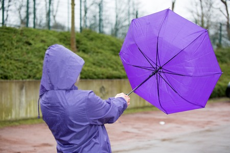 Photo for A people is fighting with an umbrella in the wind. - Royalty Free Image