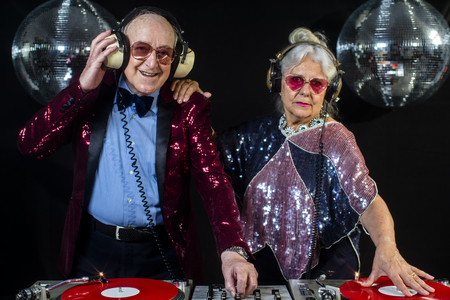 Photo for an amazing grandma and grandpa, older couple djing and partying in a disco setting - Royalty Free Image