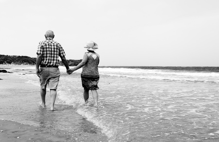 Photo pour Happy senior couple walking together on a beach - image libre de droit