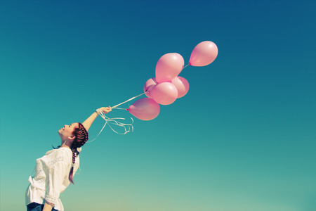Photo for Young redhead woman holding pink balloons - Royalty Free Image