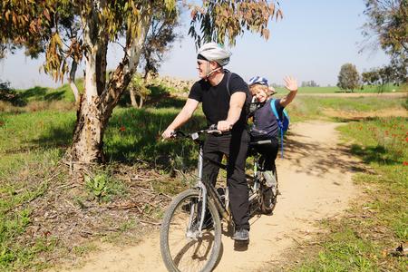 Foto de father with autistic 10 years old son ride a tandem bike - Imagen libre de derechos