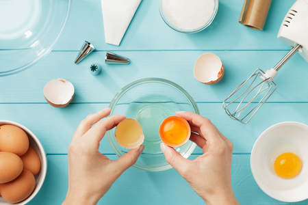 Photo for Female hands separate egg white from yolk for whipped cream. Step by step recipe of meringue with ingredients and utensils. Flat lay. - Royalty Free Image