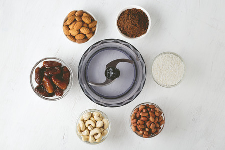 Photo for Ingredients for energy bites: nuts, dates, cocoa powder and coconut flakes with food processor on white wooden background. Step by step recipe of no bake gluten free brownie energy balls top view. - Royalty Free Image