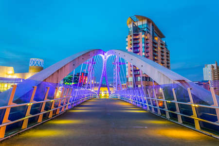 Photo for View of an illuminated footbridge in Salford quays during night in Manchester, England  - Royalty Free Image