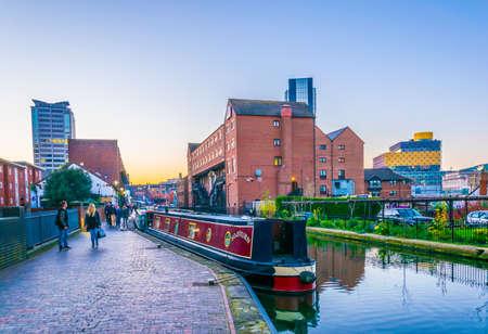 Foto de Library of Birmingham behind brick buildings alongside a water channel in the central Birmingham, England  - Imagen libre de derechos