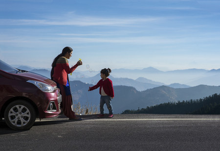 Photo pour Mother and daughter enjoying the road trip and winter vacation. Car travel vacation concept photo against Himalayan mountain in the background. - image libre de droit