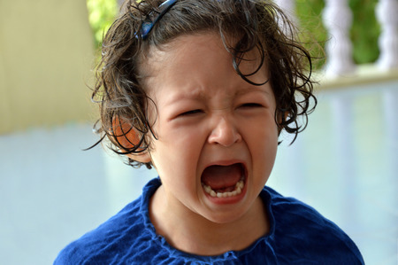 Foto de Portrait of a little toddler girl crying with mouth wide open and upset expression in the face. - Imagen libre de derechos