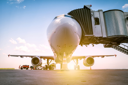 Photo pour A white passenger airplane stands at the boarding bridge and is loaded with baggage in the rays of the morning sun - image libre de droit
