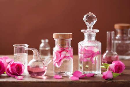 Foto de alchemy and aromatherapy set with rose flowers and flasks - Imagen libre de derechos