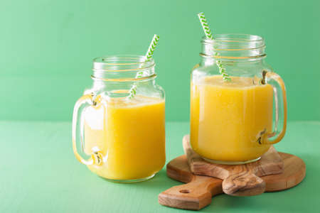 Foto de healthy mango pineapple smoothie in mason jars - Imagen libre de derechos