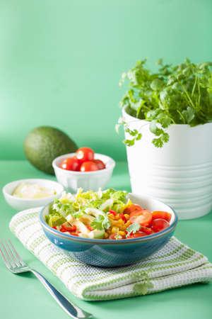 Foto de healthy vegan avocado salad with tomatoes and sweetcorn - Imagen libre de derechos