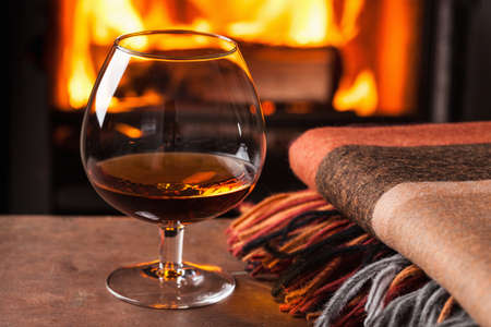 Foto de a glass of cognac in front of fireplace - Imagen libre de derechos