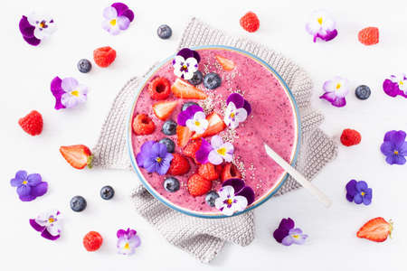 Foto de healthy summer berry smoothie bowl with flowers and chia seed - Imagen libre de derechos