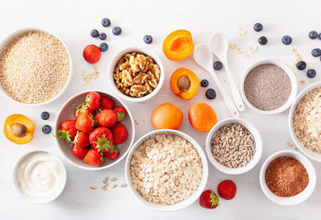Foto de variaty of raw cereals, fruits and nuts for breakfast. Oatmeal flakes and steel cut, barley, walnut, chia, apricot, strawberry. Healthy ingredients - Imagen libre de derechos