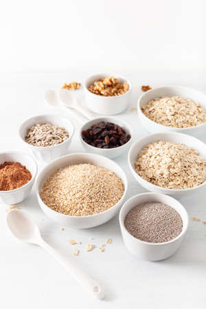 Foto de Variety of raw cereals and nuts for breakfast. Oatmeal flakes and steel cut, barley, walnut, chia, raisins. Healthy ingredients - Imagen libre de derechos