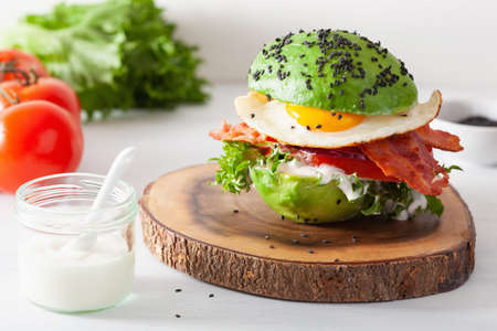 Foto de Keto paleo diet avocado breakfast burger with bacon, egg, tomato - Imagen libre de derechos