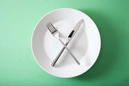 Foto per concept of intermittent fasting and ketogenic diet, weight loss. fork and knife crossed on a plate - Immagine Royalty Free