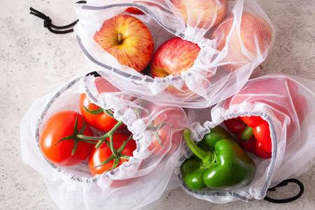 Foto de apples tomatoes bell peppers vegetables in reusable mesh nylon bag, plastic free zero waste concept - Imagen libre de derechos