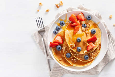 Foto de pancakes with blueberry strawberry honey and nuts for breakfast - Imagen libre de derechos