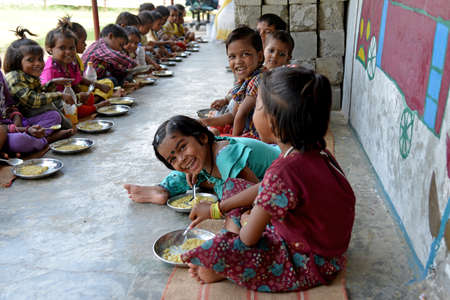 Photo pour New Delhi, India - October 5, 2015: Children are having a healthy meal at Mobile Creches, Vatika-83, Gurgaon, Delhi. Mobile Creches works with birth to 12 year old children living on the construction sites and slums since 1969 - image libre de droit