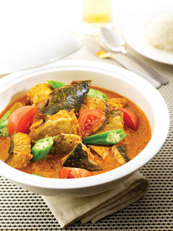 Foto de Curry Fish Head with tomatoes and herbs in white big bowl on the table - Imagen libre de derechos