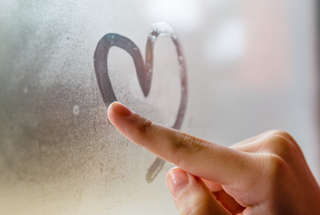 Photo for Little girl drowing heart on wet window - Royalty Free Image