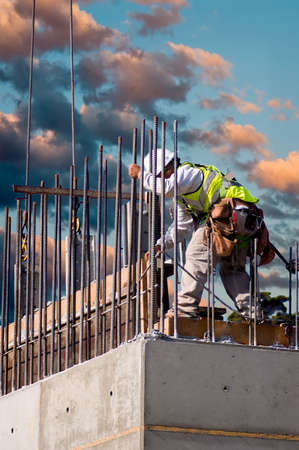 Photo pour A construction worker guiding a section into place on a high concrete wall at sunrise - image libre de droit