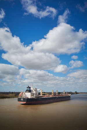 Foto per Campana River, Buenos Aires, Argentina - 22 August 2018: Big bulk carrier ship passing Campana River on her way to one of local ports on beautiful background with pretty looing clouds and sky. - Immagine Royalty Free