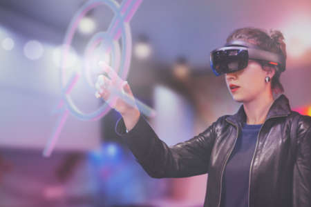 Foto de Portrait of young Caucasian woman using augmented and virtual reality with holographic hololens glasses. Pink, magenta and blue blurred background. Future technology concept. - Imagen libre de derechos