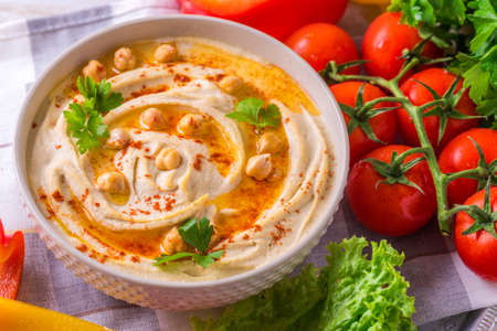 Photo for Traditional homemade hummus and chickpea served with vegetables and spices on wooden table. Jewish Cuisine. Top view - Royalty Free Image