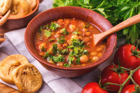 Foto de Traditional Maghreb, Moroccan and Algerian tomato soup Harira and ingredients. Served with figs. Ramadan food. Traditional Jewish cuisine - Imagen libre de derechos