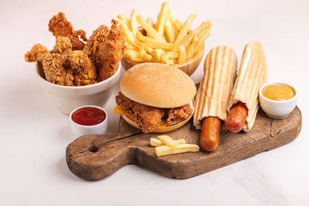 Foto per Delicious but unhealthy food with ketchup and mustard on vintage cutting board. Fast carbohydrates, junk and fast food. Light marble background. - Immagine Royalty Free