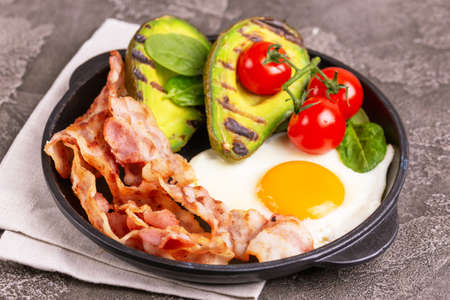 Photo for Grilled bacon and avocado, fried eggs with spinach and cherry tomatoes in cast-iron pan. Gray concrete background. Ketogenic diet. Low carb high fat breakfast. Healthy food concept - Royalty Free Image