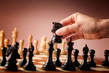Photo pour Male hand moving the black chess knight during the game of chess - image libre de droit
