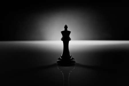 Photo pour Solitary black chess king carved in genuine ebony wood in focus standing on a glossy table in the dark - image libre de droit