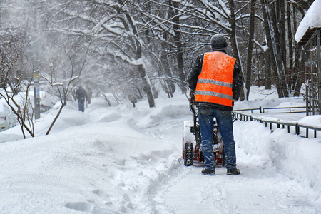 Foto de Municipal worker removing snow from the moscow street using snow blower - Imagen libre de derechos