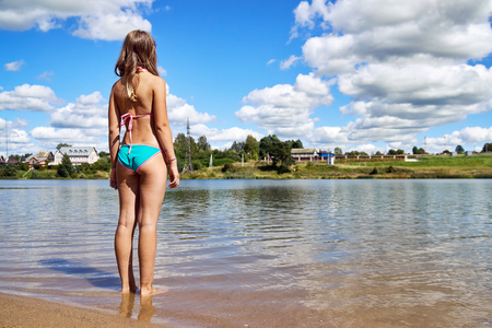 Foto de Teenager girl wearing bikini stands in the water of russian suburban lake and enjoys warm weather and is going to swim at summer vacations. Summer bathing in a country lake or pond in Russia. - Imagen libre de derechos