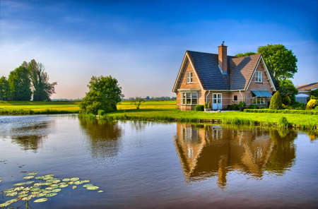 Foto de Red bricks house in countryside near the lake with mirror reflection in water, Amsterdam, Holland, Netherlands, HDR - Imagen libre de derechos