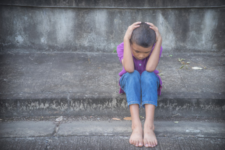 Foto de Young Asian homeless child looking scared, alone and in need of help - Imagen libre de derechos