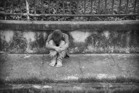 Foto de A young homeless Asian boy sitting on the side of the road covering his face. He is at high risk of abuse and trafficking - Imagen libre de derechos