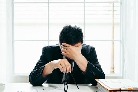 Foto de A stressed out business man holds his head in despair as he fears that he will have to file for bankruptcy or go into liquidation - Imagen libre de derechos
