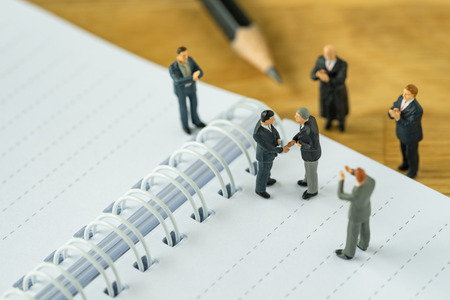 Photo for Miniature people: Small figure businessmen handshaking and others clapping on notebook and pencil as business agreement concept. - Royalty Free Image