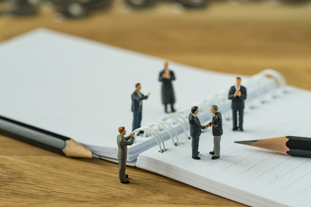 Photo for Miniature people, small figure businessman handshaking and others clapping on notebook and pencil as business agreement concept. - Royalty Free Image