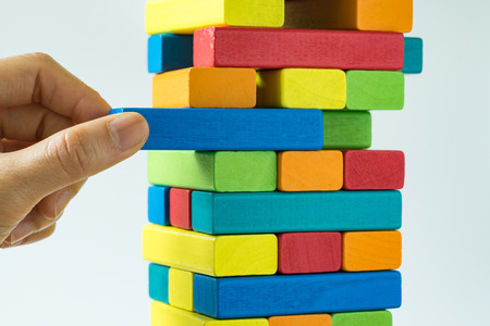 Foto de Hand pulling colorful wooden block from the tower in as Risk or stability concept. - Imagen libre de derechos