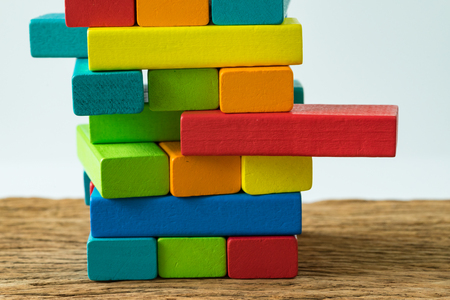 Foto de unstable colorful wooden block tower as Risk or stability concept. - Imagen libre de derechos