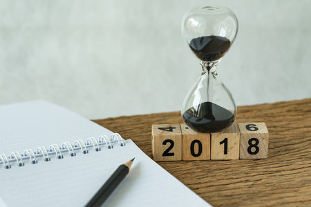 Photo pour new year 2018 goals, target or checklist concept as number 2018 wooden cube block with sandglass and white paper note with pencil on wooden table. - image libre de droit