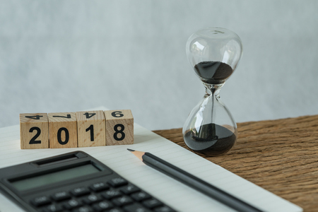 Photo pour new year 2018 goals, target or checklist concept as number 2018 wooden cube block with sandglass, white paper note, pencil and calculator on wooden table. - image libre de droit